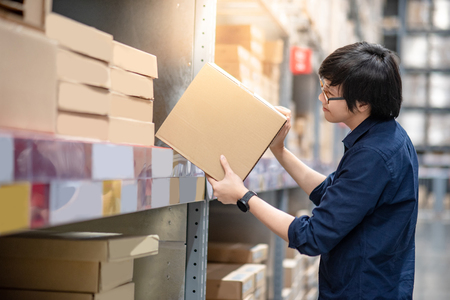 Young Asian man picking cardboard box from shelf in warehouse, shopping warehousing or packing products concepts
