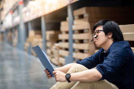 Young Asian man doing stocktaking thinking of product in cardboard box on shelves in warehouse by using paper and clipboard. physical inventory count concept Stock Photo
