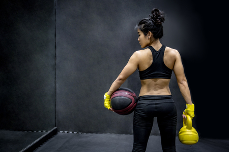 Young Asian woman in sportwear holding basketball and kettle bell on black background in the gym, sport and healthy lifestyle concepts