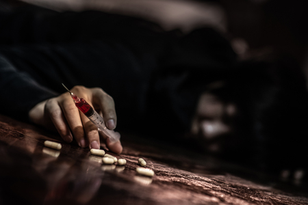 Junkie man lying on the floor while holding drug injection syringe and pills. Death drom drug overdose and addiction concept
