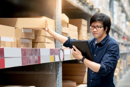 Jonge Aziatische man doet inventarisatie van product in kartonnen doos op planken in magazijn met behulp van digitale tablet. fysieke inventarisatie concept Stockfoto