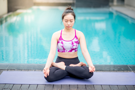 Young Asian attractive woman doing yoga exercise with padmasana posing or lotus position pose near swimming pool. Pilates workout and healthy lifestyle concepts