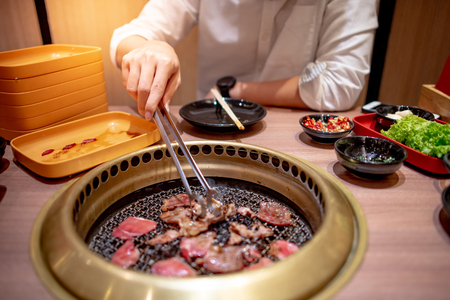 Young Asian man eating Korean Barbecue buffet grilling beef in the restaurant