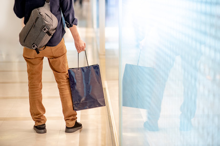 Closeup of male hand holding blue shopping bag in department store. Urban lifestyle in shopping mall concept Stock Photo