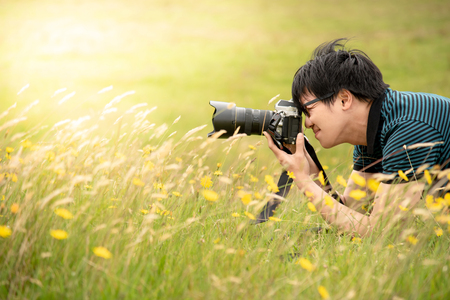 Young Asian male photographer taking photo by DSLR camera on green field. Nature and landscape photography