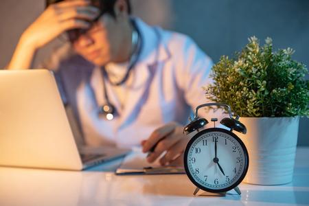 Überarbeiteter Arzt, der mit Laptop in der Krankenhausklinik arbeitet. Männliche Praktizierende fühlen sich während der harten Arbeitszeit im medizinischen Zentrum gestresst und versucht. Fokus auf Tischuhr.