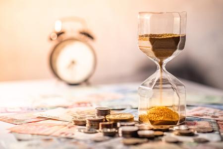 Sand läuft durch die Form der Sanduhr auf dem Tisch mit Banknoten und Münzen der internationalen Währung. Zeitinvestition und Altersvorsorge. Dringlichkeits-Countdown-Timer für das Geschäftsschlusskonzept Standard-Bild