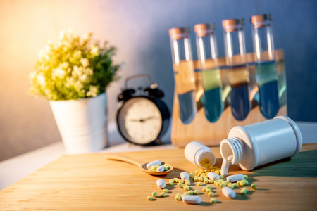 Pills spilling out of pill bottles with pharmaceutical spoon on wooden board. Table clock and test tube in the background. Prescription medicine and medical treatment concepts
