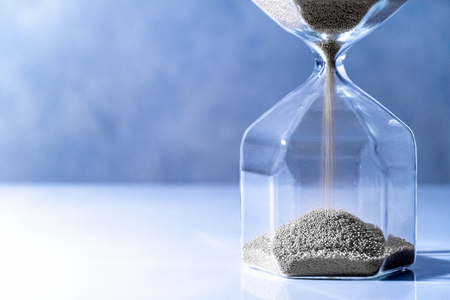 Sliver sand running through the shape of modern hourglass on white table.Time passing and running out of time. Urgency countdown timer for business deadline concept Banco de Imagens