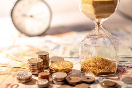 Sand running through the shape of hourglass on table with banknotes and coins of international currency. Time investment and retirement saving. Urgency countdown timer for business deadline concept 免版税图像
