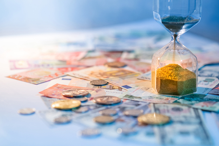 Sand running through the shape of hourglass on table with banknotes and coins of international currency. Time investment and retirement saving. Urgency countdown timer for business deadline concept Stock Photo