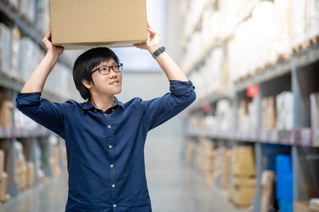 Young Asian man carrying cardboard box over head between row of shelves in warehouse, shopping warehousing or working pick and packing concepts