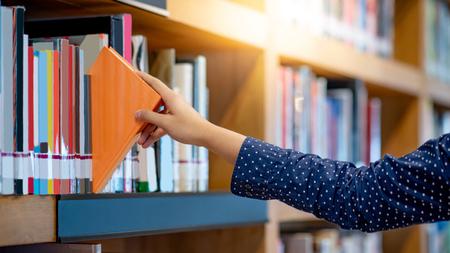 Mano derecha masculina eligiendo y recogiendo libro naranja en la biblioteca pública. Sacando el libro de texto seleccionado. La investigación educativa y el autoaprendizaje en los conceptos de la vida universitaria Foto de archivo