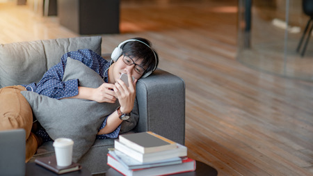 Young Asian man using smartphone for listening to music on mobile application, lying and relaxing on sofa during free time. Urban lifestyle in living space concept Stock Photo