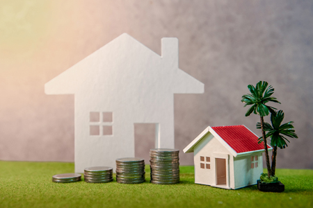 Real estate investment or Home mortgage loan rate. Property ladder concept. Coins stack, house model and table clock on green grass. Investment and business growth background