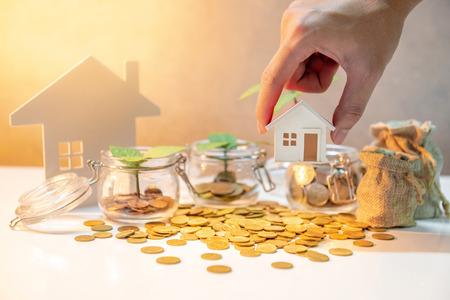 Propriété ou investissement immobilier. Taux de prêt hypothécaire à domicile. Économiser de l'argent pour le futur concept. Male hand holding house medel sur pot en verre de monnaie, sacs d'argent et pièce d'or se répandant sur la table