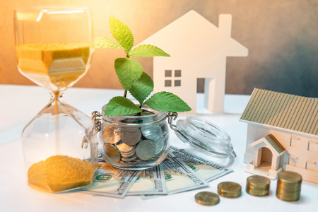 Real estate investment or property ladder. Home mortgage loan rate. Saving money for future concept. Plant growing out of coins in glass jar with dollar banknotes, hourglass and house model on table