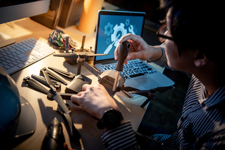 Asian technical engineer using screwdriver for repairing drone with computer and other tools on desk. Male technician fixing or maintenance drone. Unmanned aerial vehicle (UAV) photography concept
