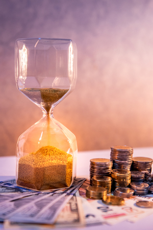 Sand running through the shape of hourglass with banknotes and coins stack of international currency on table. Time investment. retirement saving. Urgency countdown timer for business deadline concept Stock Photo