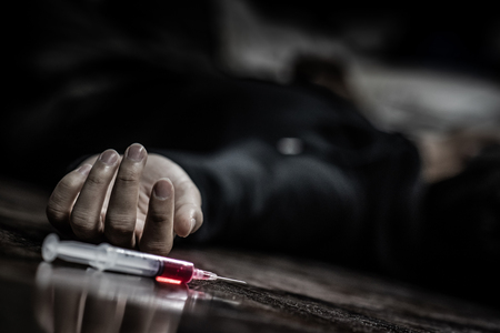 Junkie man lying on the floor near drug injection syringe. Death from drug overdose and addiction concept Stock Photo