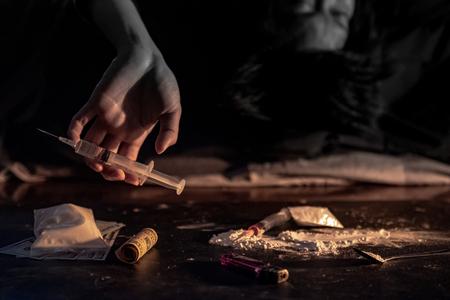 Mano masculina drogadicta que sostiene la jeringa de inyección de drogas mientras está acostado cerca de la heroína en polvo, una cuchara y un encendedor para cocinar con heroína y dinero en el piso oscuro. Concepto de adicción a las drogas duras Foto de archivo