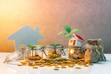 Property or real estate investment. Home mortgage loan rate. Saving money for future concept. Plant growing out of currency glass jar with house model, money bags and gold coin spilling on the table Foto de archivo