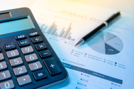 Calculator, pen and summary report paperwork with bar graph, pie chart and table. Financial data analysis. Business planning and management concept