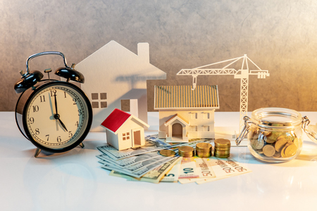 Real estate or property development. Construction business investment concept. Home mortgage loan rate. Coin stack on international banknotes with clock, house and crane models on the table. 스톡 콘텐츠
