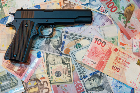 Black gun on various of international banknotes. illegal arms trafficking concept Foto de archivo