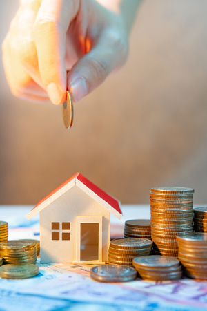 Real estate or property investment growing business. Home mortgage loan rate. Saving money for retirement concept. male hand holding coin over house model and coin stack on international banknotes Banque d'images