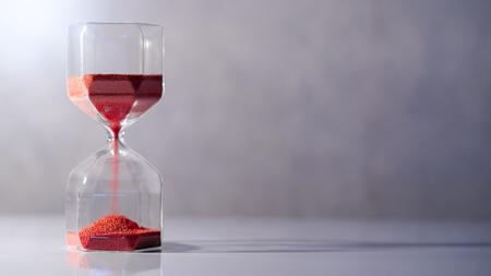 Roter Sand läuft durch die Form der modernen Sanduhr auf weißem Tisch. Zeit vergeht und läuft die Zeit davon. Dringlichkeits-Countdown-Timer für Geschäftsschlusskonzept mit Kopierplatz