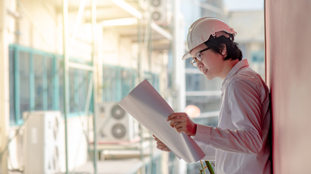 Young Asian Engineer or Architect holding files while wearing personal protective equipment safety helmet at construction site. Engineering, Architecture and construction business concepts