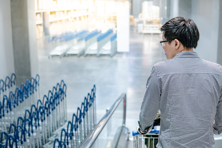 Young Asian man shopper holding shopping cart (trolley) on travelator (escalator) in supermarket or grocery store. Shopping lifestyle concept Stock Photo
