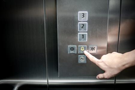 Mannelijke wijsvinger die op noodstop en alarmknop in lift (lift) drukt. Werktuigbouwkunde concept Stockfoto