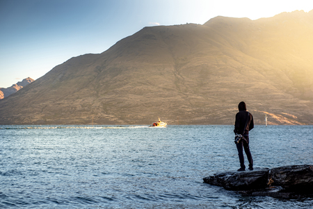 Male travler standing on the rock looking at mountain scenery during sunset at Lake Wakatipu in Queenstown, South Island, New Zealand. Travel concept