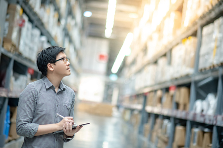 Young Asian man worker doing stocktaking of product in cardboard box on shelves in warehouse by using digital tablet and pen. Physical inventory count concept Stock fotó