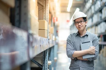 Joven trabajador asiático con casco de seguridad y anteojos haciendo inventario del producto en caja de cartón en los estantes del almacén mediante tableta digital y bolígrafo. Concepto de recuento de inventario físico