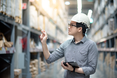 Young Asian man worker wearing safety helmet and eyeglasses doing stocktaking of product in cardboard box on shelves in warehouse by using digital tablet and pen. Physical inventory count concept