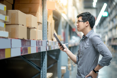 Young Asian man worker doing stocktaking of product in cardboard box on shelves in warehouse by using digital tablet and pen. Physical inventory count concept Stockfoto