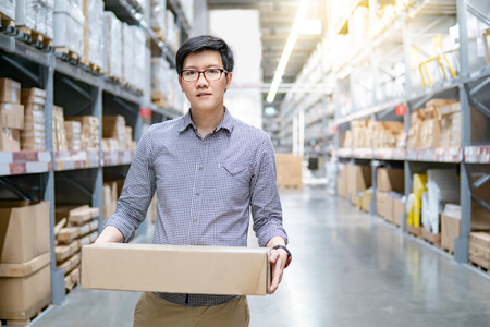 Young Asian man carrying cardboard box between row of shelves in warehouse. Shopping warehousing or working pick and packing concepts Banque d'images