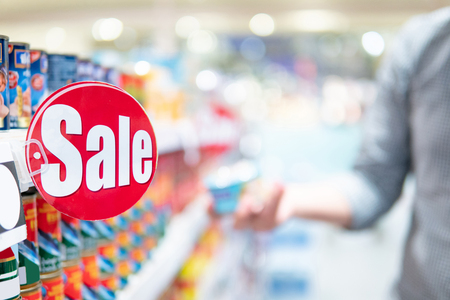 Etiqueta de venta roja en el estante del producto en el supermercado con un comprador masculino borroso que elige el paquete de alimentos en el fondo. estilo de vida de compras en concepto de tienda de comestibles
