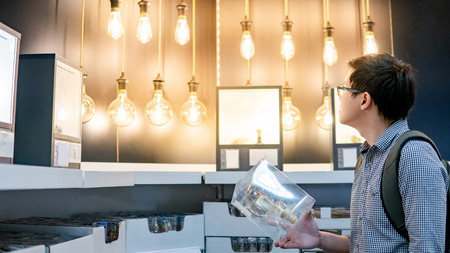 Young Asian man choosing package of electrical light bulb in the store. Furniture home decoration shopping concept