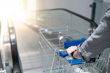 Male hand shopper holding shopping cart (trolley) on travelator (escalator) in supermarket or grocery store. Shopping lifestyle concept