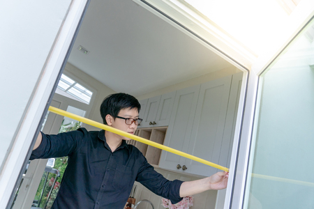 Young Asian worker man using tape measure on door frame in the kitchen. Home interior designer measuring elements on site. Housing design and construction concept Standard-Bild
