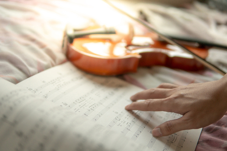 Musician hand on sheet of music note and vintage violin on flowery pink bed in the bedroom. Playing music instrument at home concept