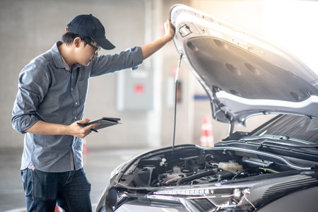Asian auto mechanic holding digital tablet checking car engine under the hood in auto service garage. Archivio Fotografico