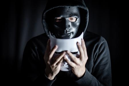 Mystery hoody man wearing broken black mask holding white mask. Anonymous social masking. Major depressive disorder or bipolar disorder. Halloween concept