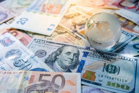 Economía y negocios globales. Vaso de cristal de globo del mundo en varios billetes de dinero internacional. Tasa de cambio de moneda. Concepto de inversión financiera