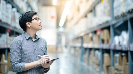 Joven trabajador asiático haciendo inventario del producto en caja de cartón en los estantes del almacén mediante tableta digital y lápiz. Concepto de recuento de inventario físico