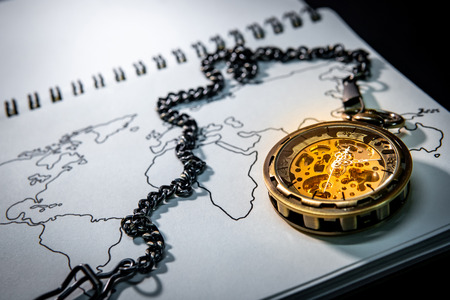 Gold pocket watch on world map outline sketch on paper page of notbook. Travel around the world. Global business concept